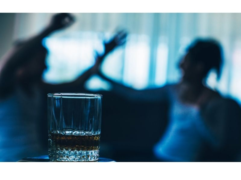 couple fighting with glass with alcoholic drink on foreground